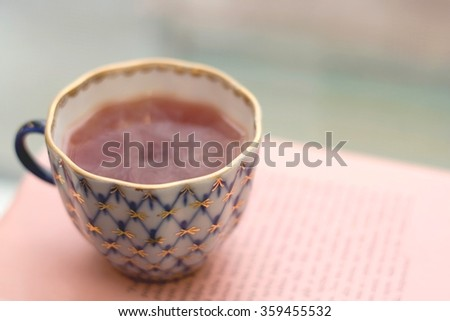 Tea in a vintage porcelain cup on a pile of old books near the window. Shallow depth of field and soft focus. - stock photo