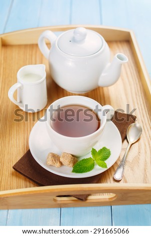 Tea in a white cup with mint, and two lumps of sugar. Morning tea with cream and mint. - stock photo
