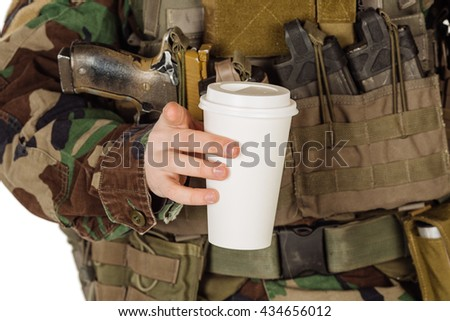 Tea in a white paper cup in the hands of a soldier - stock photo