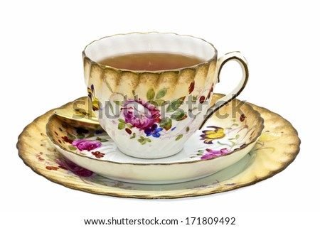 Tea in an antique china cup with saucer and dessert plate. - stock photo