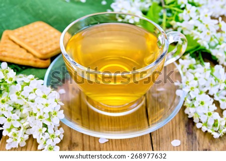 Tea in glass cup with shortbread, napkin, twigs with flowers of bird cherry on a background of a wooden board - stock photo