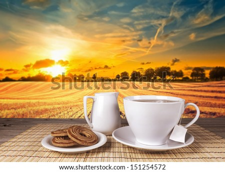 Tea in white cup ceramic old wooden table with view landscape - stock photo