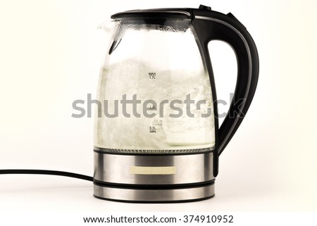 Tea kettle with boiling water isolated on white / Water boiling in the glass electric kettle - perfect close up - stock photo