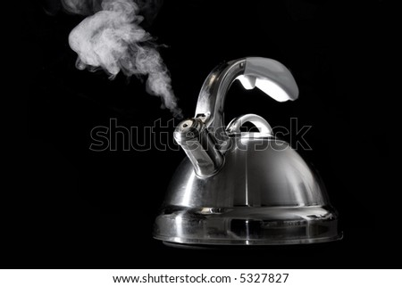 Tea kettle with boiling water on black background. - stock photo