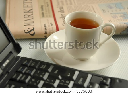Tea, laptop and business newspaper - stock photo