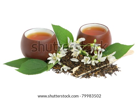 Tea leaves with fresh jasmine flowers and chinese cups on white background - stock photo