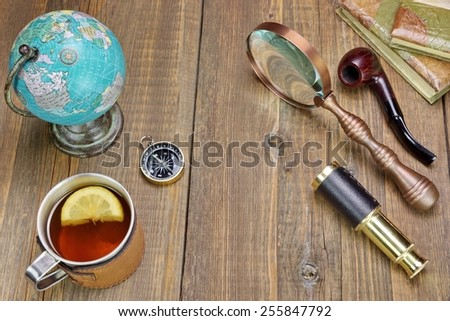 Tea Mag On Grunge Wood Table With Many Travel Objects. Compass, Spyglass, Vintage Notebooks, Bell, Retro Globe Map, Smoking Pipe, Magnifying Glass - stock photo