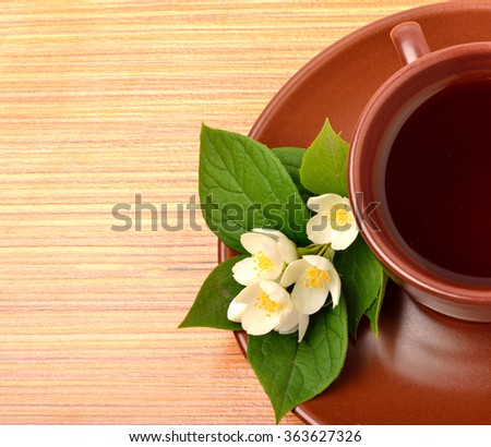 Tea on the ceramic cup with jasmine flower on the wooden background - stock photo