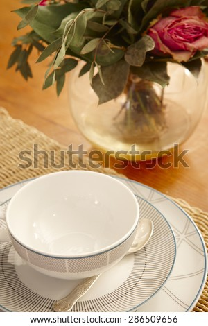 Tea or coffee cup and table with roses still life. Vertical - stock photo