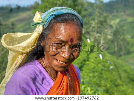 Tea picker smiles at the camera.