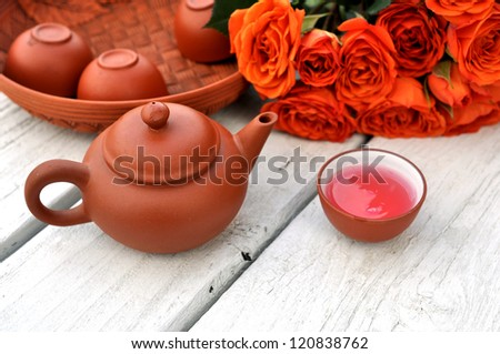tea pot and bunch of rose in garden - stock photo