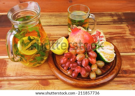 tea pot and fruits on wooden table - stock photo
