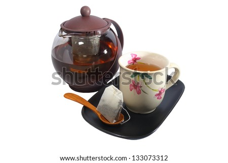 Tea pot with a cup of tea on white background - stock photo