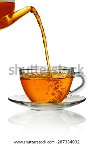 Tea pouring into glass cup isolated in white - stock photo