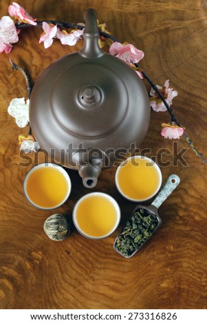 tea set (teapot, cups and different green tea) on a wooden background - stock photo