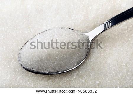 Tea spoon of white granulated sugar - stock photo