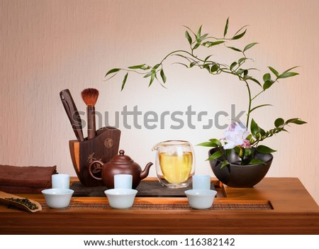 Tea still life: flowers , kettle, cups, pile of dry tea. - stock photo