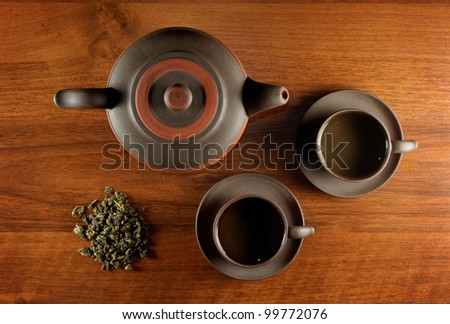 tea still life with kettle, cups and dry tea in heap, all on wooden desk - stock photo