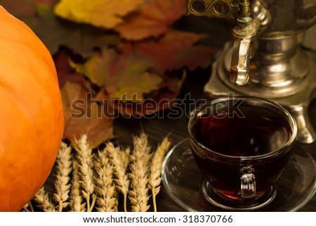 Tea still life with samovar, ripe orange pumpkins, maple leaves, wheat on wooden background. Thanksgiving, autumn. - stock photo