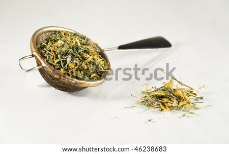 Tea-strainer full of colorful herbs, isolated on white - stock photo