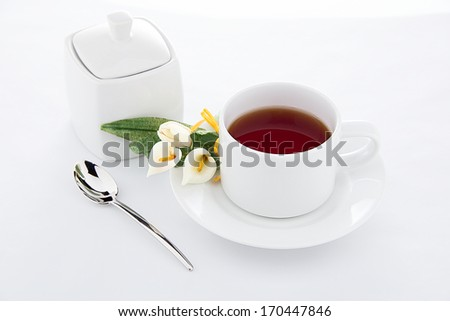 Tea time - a cup of tea with sugar pot and flowers - stock photo