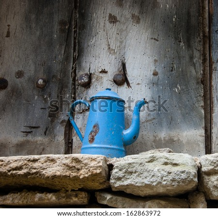 Tea time. Destruction concept. Old iron teapot with peeling paint isolated on the rough sandstone bricks against grungy wooden background. - stock photo