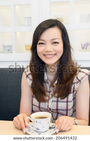 Tea time, elegant Asian woman with a cup of tea in a restaurant.