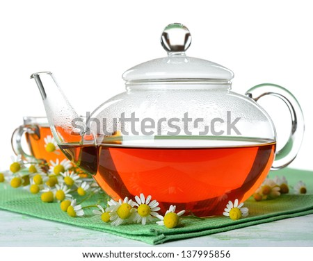 Tea with chamomile  in a glass teapot on a white background - stock photo