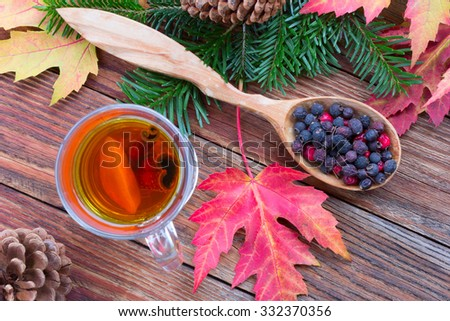 tea with cinnamon and lemon, colorful autumn leaves of maple, hawthorn berries in a wooden spoon, ripe apples and spruce branches with cones on a wooden table close-up view from above - stock photo