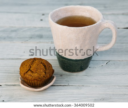 Tea with cupcake. pumpkin cupcake,  cup of coffee, cupcake on the table, clay dishes, coffee and cupcake. - stock photo