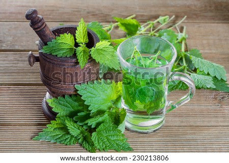Tea with fresh nettles on a wooden background  - stock photo