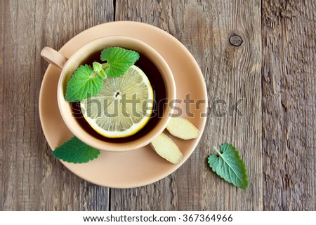 Tea with lemon, ginger and mint leaves in cup over rustic wooden background with copy space - stock photo