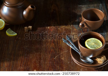 Tea with lemon. Tableware from dark ceramics. Cup of tea and teapot on old wooden table. - stock photo