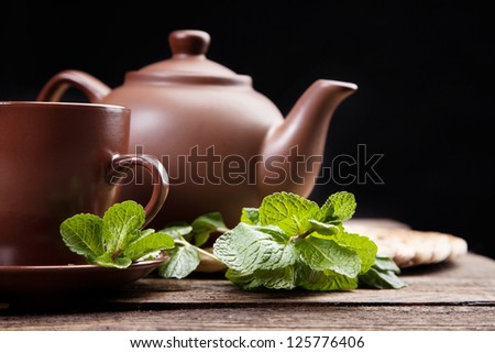 Tea with mint on a wooden table - studio still life - stock photo