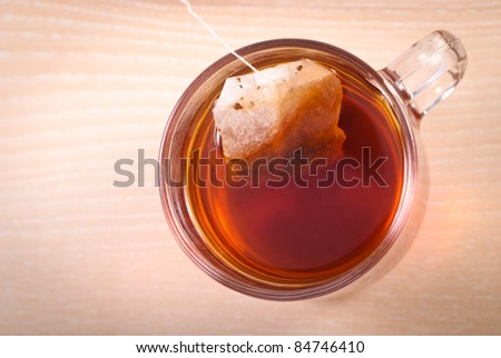 teabag in cup with tea on wooden table - stock photo