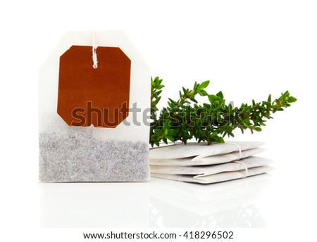 Teabag with green thyme herbs. Isolated on white background - stock photo