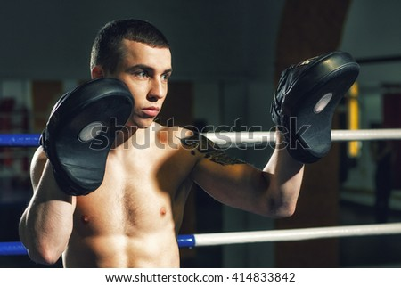 Teach and learn. Young athlete holding boxing paws in a ring. - stock photo