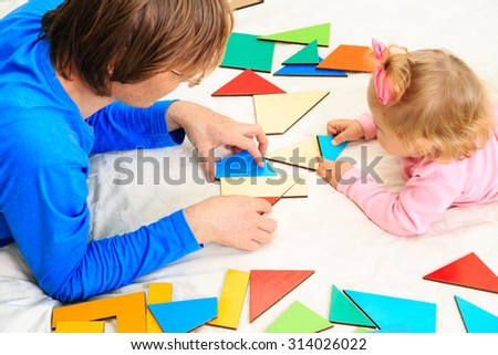 teacher and child playing with geometric shapes, early learning - stock photo