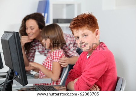 Teacher and children learning to use computer - stock photo