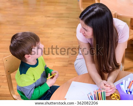 Teacher and cute boy Looking at Each Other - Supporting Child - stock photo