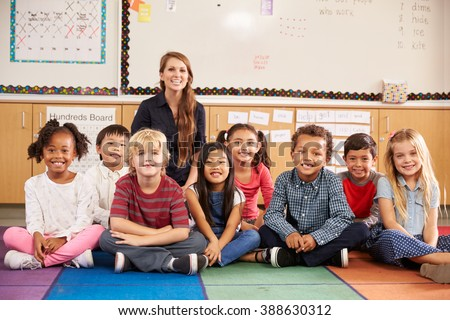Teacher and elementary school kids sitting on classroom floor - stock photo
