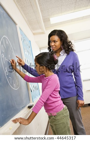 Teacher and female student at the blackboard with clock drawing on it. - stock photo