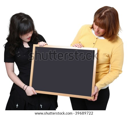 Teacher and highschool student holding chalkboard over white.  Looking at chalkboard. - stock photo