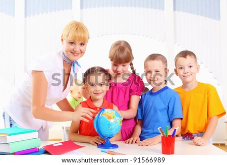 teacher and his students are studying a globe - stock photo