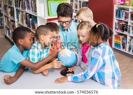Teacher and kids discussing globe in library at school