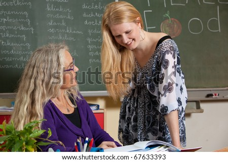 Teacher and one of her students in the class room - stock photo