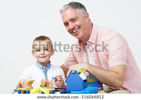 Teacher And Pre School Pupil Playing With Wooden Tools - stock photo