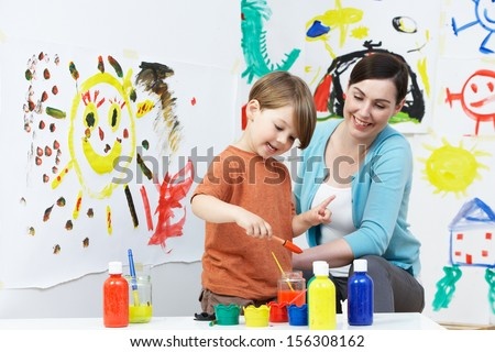Teacher And Pupil In Pre School Art Class - stock photo