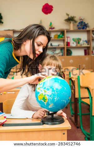 Teacher and pupil in the classroom looking at a globe