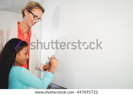 Teacher and pupil writing on whiteboard at school - stock photo